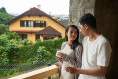Morning of young couple. Young couple drinking water when standing on balcony in the morning Stock Photos