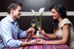 Young couple drinking wine and flirting. Attractive young couple drinking wine and flirting Stock Photography