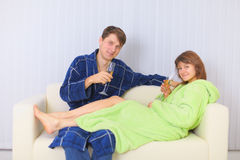Young couple drinks sparkling wine on sofa Royalty Free Stock Photos