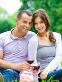 Young couple drinks wine in park Royalty Free Stock Photo