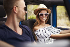 Young Couple Driving Open Top Car On Country Road Stock Photos
