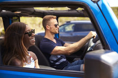 Young Couple Driving Open Top Car On Country Road Stock Images