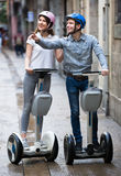 Young couple driving segways. Cheerful young couple driving segways along the city  and seeing sights Stock Image