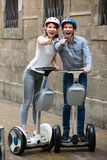Young couple driving segways. Cheerful young couple in helmets driving segways along the city Stock Photos