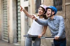 Young couple driving segways. Happy young couple driving segways along the city  and seeing sights Stock Images