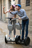 Young couple driving segways. Positive young couple driving segways along the city  and seeing sights Stock Image