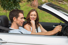 Young couple driving in a silver convertible Royalty Free Stock Photo