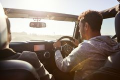 Young couple driving with sunroof open, rear passenger POV royalty free stock image