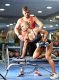 Young couple with dumbbell flexing muscles in gym Stock Photos