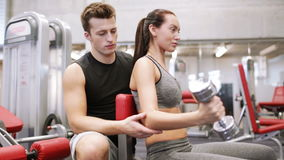 Young couple with dumbbell flexing muscles in gym. Fitness, sport, exercising and weightlifting concept - young woman and personal trainer with dumbbells flexing stock video footage