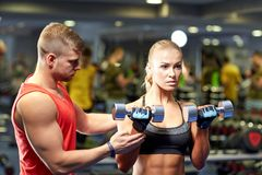Young couple with dumbbells flexing muscles in gym Royalty Free Stock Photos