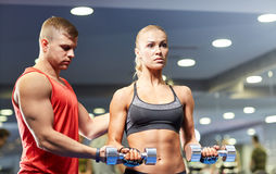 Young couple with dumbbells flexing muscles in gym Stock Image
