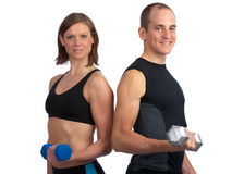 Young couple with dumbells. Young, caucasian couple working out with dumbells, smiling at camera Stock Photos
