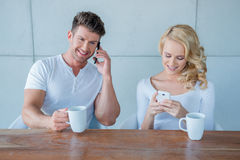 Young couple each using their mobile phone Stock Image