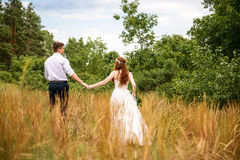 Young couple in the ears of wheat in forest Stock Images