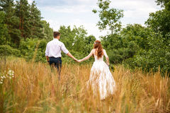 Young couple in the ears of wheat in forest Stock Photos