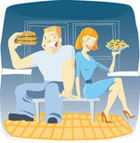 Young couple eating. Woman with salad and man with hamburger in cafe Stock Photography
