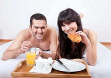 Young couple eating breakfast in bed Stock Images