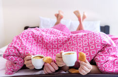 Young couple eating breakfast in bed . Stock Photo
