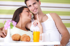 Young couple eating breakfast in bed. Lovely young couple having breakfast in bed Stock Photo