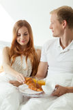 Young couple eating breakfast in bed Royalty Free Stock Photo