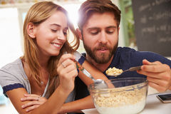Young Couple Eating Breakfast In Kitchen Together Stock Photo