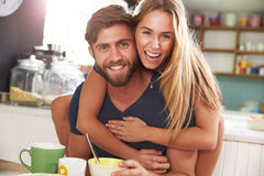 Young Couple Eating Breakfast In Kitchen Together Stock Image