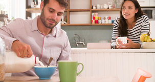 Young Couple Eating Breakfast In Kitchen Together Stock Images