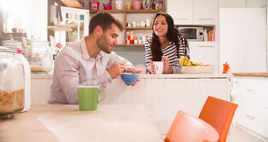 Young Couple Eating Breakfast In Kitchen Together Stock Photography