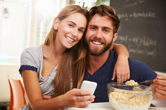 Young Couple Eating Breakfast Whilst Using Mobile Phones Royalty Free Stock Photo