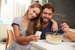 Young Couple Eating Breakfast Whilst Using Mobile Phones Royalty Free Stock Photos