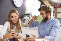 Young Couple Eating Breakfast Whilst Using Mobile Phones Stock Photos