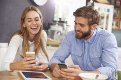 Young Couple Eating Breakfast Whilst Using Mobile Phones Stock Photo