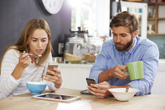 Young Couple Eating Breakfast Whilst Using Mobile Phones Stock Photography