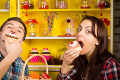 Young Couple Eating Cake at the Cafe. Young Couple Doing Eating a Cake Pose at the Cafe While looking at the Camera. Captured with Candy Jars Display at the Back stock image