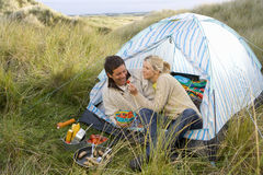 Young couple eating at campsite Stock Photography