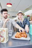 Young couple is eating croissants in bistro stock image