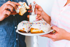 Young couple eating donuts. A young couple in a studio eating donuts and drinking milk Royalty Free Stock Photography
