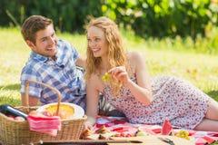 Young couple eating grapes at a picnic Royalty Free Stock Image