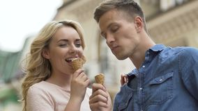 Young couple eating ice-cream and laughing, enjoying romantic date, close-up