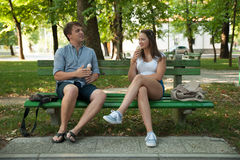 Young couple eating ice cream in shadow on a bench in park on ho Stock Photography