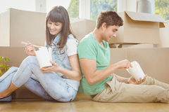 Young couple eating noodle. Young couple sitting on the floor and eating noodle in their new house Royalty Free Stock Photo