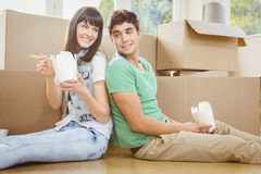 Young couple eating noodle. Young couple sitting on the floor and eating noodle in their new house Stock Image