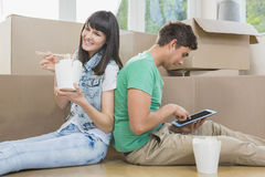 Young couple eating noodle and using digital tablet. In their new house Stock Photo
