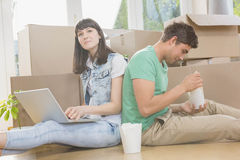 Young couple eating noodle and using laptop Stock Photography