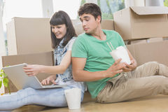 Young couple eating noodle and using laptop. In their new house Stock Images