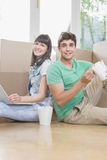 Young couple eating noodle and using laptop. In their new house Stock Photography