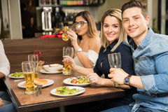 Young couple eating out with friends stock images