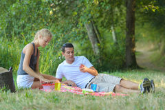 Young couple eating at picnic in park Stock Photography