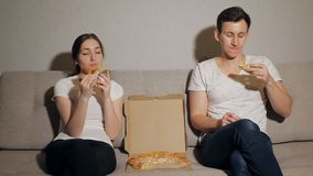 Young couple eating pizza. Drinking, talking and smiling stock video footage